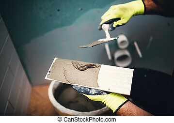 industrial close up detail of worker adding cement adhesive on small ceramic tiles