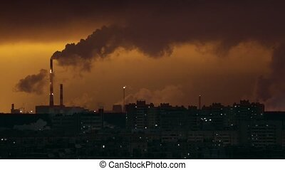 Industrial concept. Rows of buildings. Industrial pipes exhales the smoke. Lights from the windows