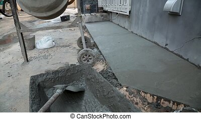 Cement mixer on construction site is mixing concrete. -...