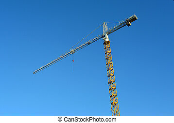 Industrial construction crane against blue sky in the background