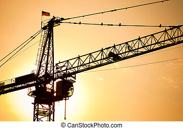 Industrial construction crane over sun at sunset