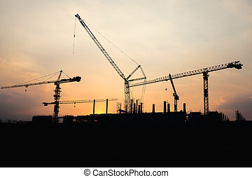 Industrial construction crane working and building at site on sunset time