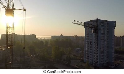 Industrial construction cranes and building silhouettes over sun at sunrise