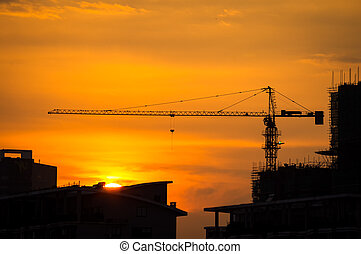 Industrial construction cranes and building silhouettes with sunset