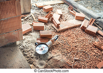 Industrial construction site tools, angle grinder used for cutting bricks at building renovation, reconstruction