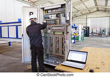 Industrial control panel - Man worker checking advanced...
