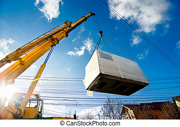 Industrial Crane operating and lifting an electric generator against sunlight and blue sky