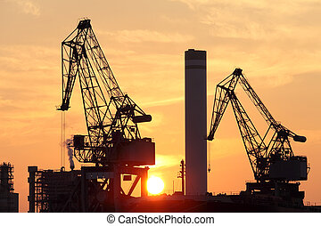 industrial cranes at sunset