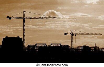 Crane silhouettes against the skyline
