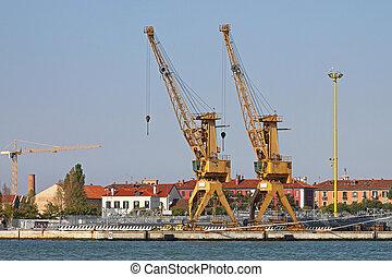 Two yellow industrial cranes in Venice harbor