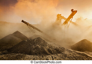Industrial hell pollution background concept - crusher rock stone crushing machine at open pit mining and processing plant for crushed stone, sand and gravel on sunset