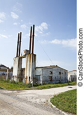 Decaying industrial building against bright blue sky