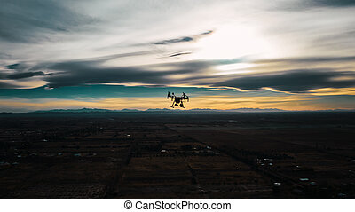 industrial drone flying at sunset