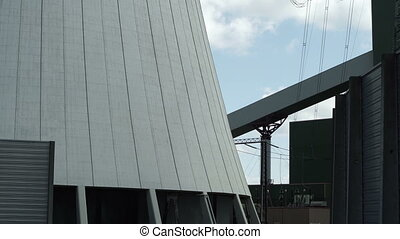 Industrial Electrical Pylon Shadow Appears on Cooling Tower