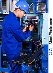 industrial engineer repairing computerized machine