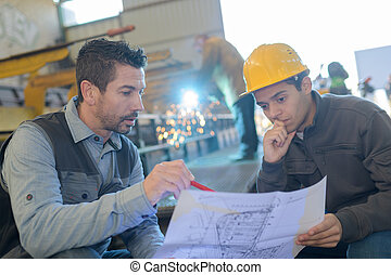 industrial engineer showing a plan to his manager