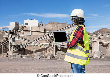 Industrial engineer using laptop on construction site