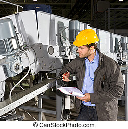Industrial equipment check - A maintenance engineer checking...
