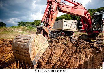 industrial excavator digging a hole and loading earth