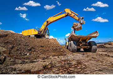 industrial excavator loading soil from sandpit into a dumper...