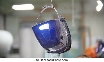 Industrial factory. Taking a helmet from the hook