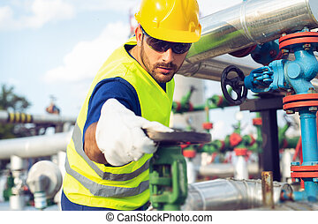 Industrial factory worker turning valve