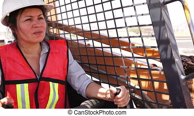 Female in white hard hat and orange safety vest operating an earthmoving skid-steer loader and turning to the camera to smile.
