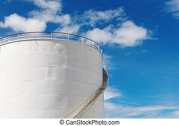 Industrial fuel tank against blue sky background