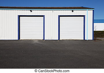 Two closed white corrugated industrial garage doors in a small warehouse and open tarmac in the foreground against blue sky.