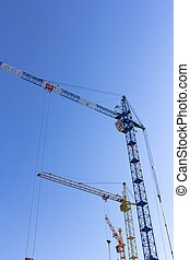 Industrial landscape, building crane against the blue sky