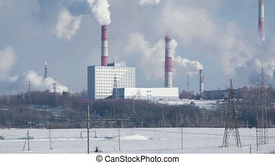 Industrial landscape, plant with smoking pipes and gas torches