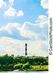 Industrial landscape with clouds and greenery. - Chimney of...