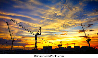Industrial landscape with silhouettes of cranes on the sunset ba