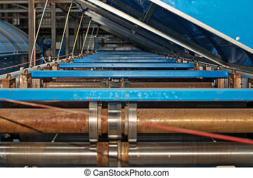 Industrial machine for the production of metal roofing