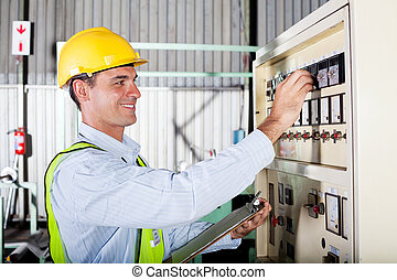 operator adjusting machine settings - industrial machine ...
