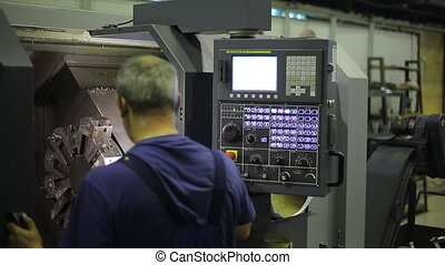 Industrial Machine Operator. Console for controlling an industrial machine. Male worker using industrial control panel of a industrial machine.