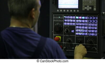 Industrial Machine Operator. Male worker using industrial control panel of a industrial machine. Console for controlling an industrial machine.