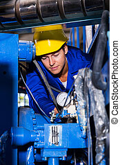 industrial machine operator checking on machinery