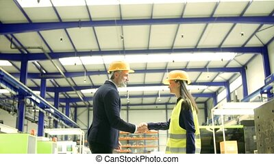 Industrial man and woman engineers in a factory, shaking...