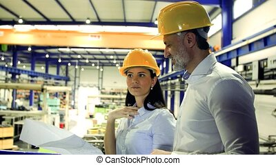 Industrial man and woman engineers looking at blueprints.