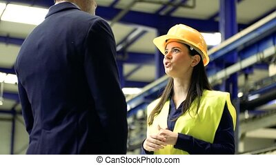 Industrial man and woman engineers standing in a factory, talking.