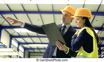 Industrial man and woman engineers with clipboard in a factory, working.