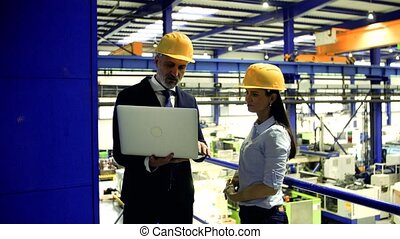 Industrial man and woman engineers with laptop in a factory working.