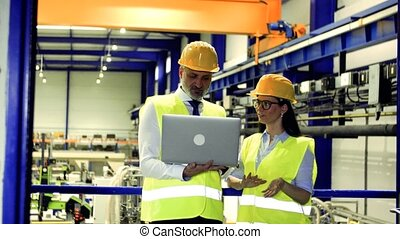 Industrial man and woman engineers with laptop in a factory, working.