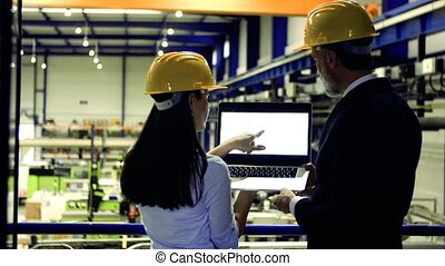 Industrial man and woman engineers with laptop in a factory,...