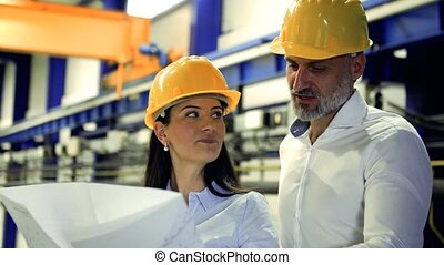 Industrial man and woman engineers with yellow helmets...