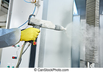 industrial metal coating. Worker man in protective suit with gas mask spraying powder to steel finished parts in painting chamber