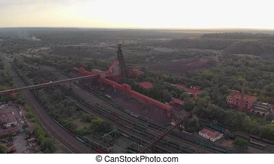 Industrial mining quarry red iron ore headframe aerial drone takeoff up camera movement Krivoy Rog Ukraine