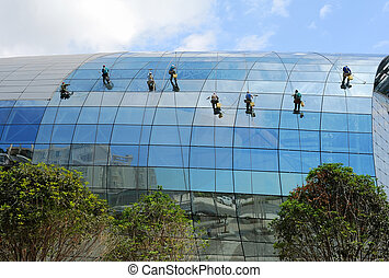 Industrial mountaineering workers wash windows of a high-rise building