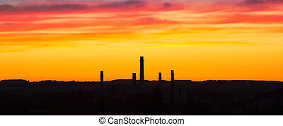 Industrial panorama on the background of a colorful dramatic sky with clouds at sunset.
